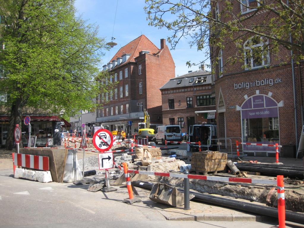 Bager Wendorff i Asylgade (ses under træet til venstre i billedet) er én af de forretningsdrivende, der nu forventes at være positiv stemt overfor kommunen. For blot to uger siden var hans butik helt blokeret af - strategisk - vejarbejde. Foto: maj 2014.